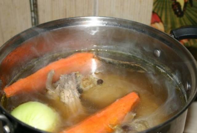 Чистим лук, корень петрушки и морковь. Разрезаем на 4 части и добавляем в куриный бульон. Туда же отправляем отваренные грибы вместе с отваром. Солим, добавляем перец и варим до готовности курицы. Затем вареные овощи необходимо удалить. Добавляем лавровый лист и выключаем огонь.