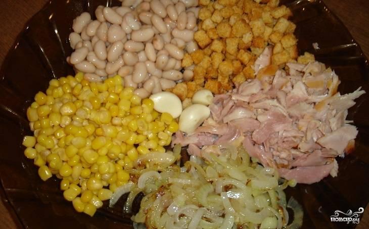 2.Открываем банки с кукурузой и фасолью, сливаем с них лишнюю жидкость. Фасоль откидываем на сито и немного промываем в теплой воде. Окорок очищаем, нарезаем мелко мясо. Чистим чеснок и измельчаем через пресс или натираем на терке.