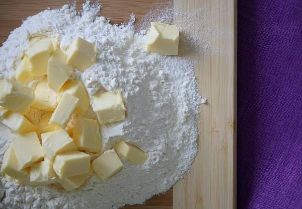 1. Муку просеять с разрыхлителем и солью на рабочий стол. Сливочное масло, предварительно достав из холодильника, порубить небольшими кубиками. Использовать в рецепт приготовления швабского пирога со смородиной маргарин не стоит.