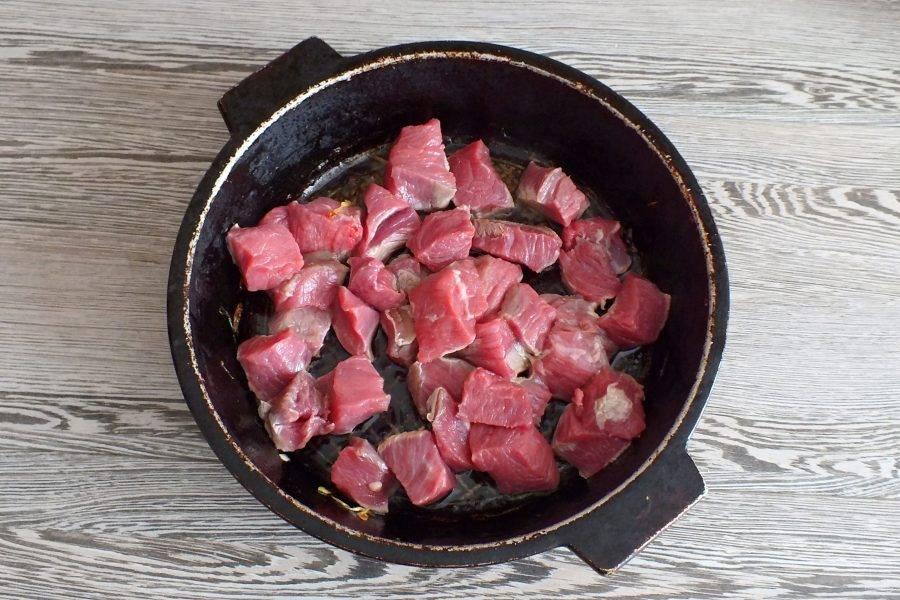 В жаровню выложите нарезанное мясо. Если масла совсем не осталось после обжаривания овощей, добавьте пару столовых ложек. Обжаривайте говядину, периодически помешивая, до исчезновения жидкости.