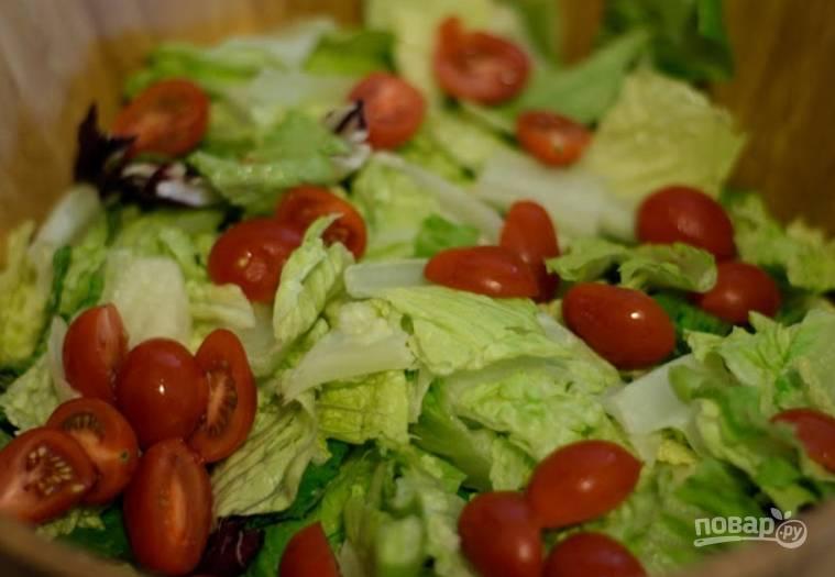 Моем помидоры черри и разрезаем их на половинки. Добавляем в салатницу.