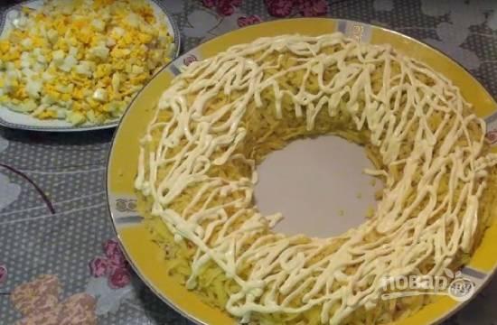 Смазываем картофельный слой. Яйца очистим и нарежем на мелкие кубики.