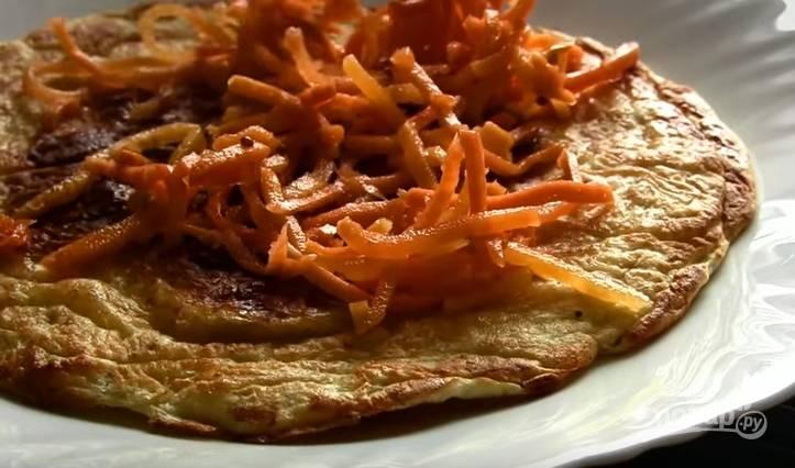5. Теперь начните собирать торт. На блинчик выложите слой корейской морковки. И чередуйте эти слои. На верхний блин выложите тертый сыр.
