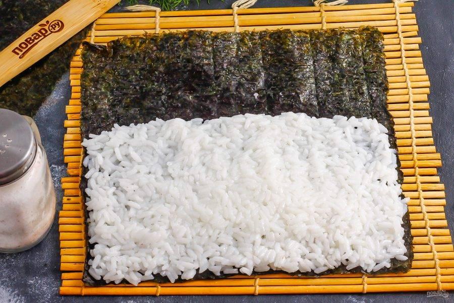 Расстелите коврик, а на него выложите лист нори. Смочите руки в воде и выложите на нори отварной рис, стараясь не заполнять водоросли с одного края на 2-3 см.
