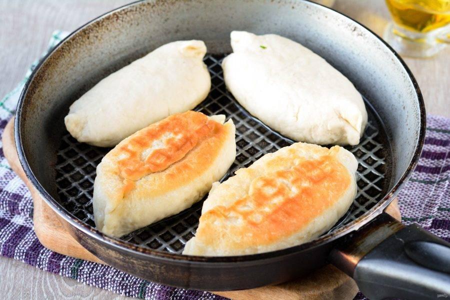 Обжарьте пирожки с двух сторон на сковороде с добавлением растительного масла. Жарьте по 3-4 минуты с каждой стороны, тесто должно хорошо прожариться.