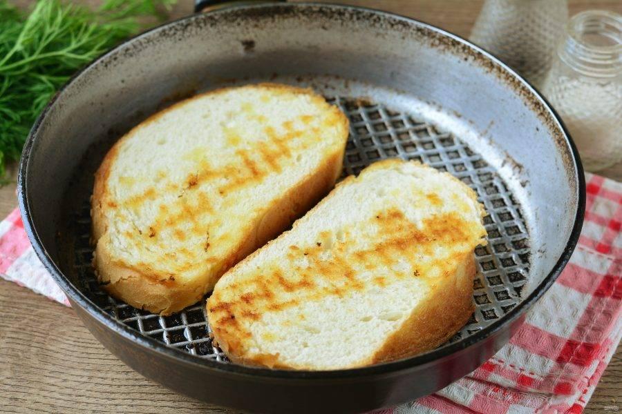 Обжарьте кусочки батона на сухой сковороде с двух сторон до румяной корочки.