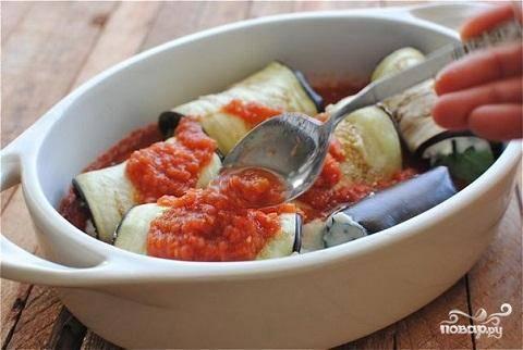 4.Сверните пластины рулетами. В форму для запекания на дно вылейте немного томатного соуса. Рулетики  положите в соус швом вниз. Вылейте сверху оставшийся соус.