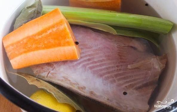 Морковь очистите, помойте и нарежьте большими кусками вместе с лимоном и луком. Эти ингредиенты, а также рыбу, лавровый лист и перцы залейте двумя литрами воды в кастрюле.