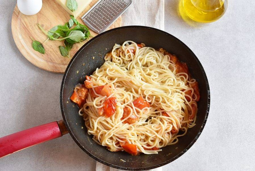 Сразу же выложите пасту в сковороду к помидорам и хорошо перемешайте.