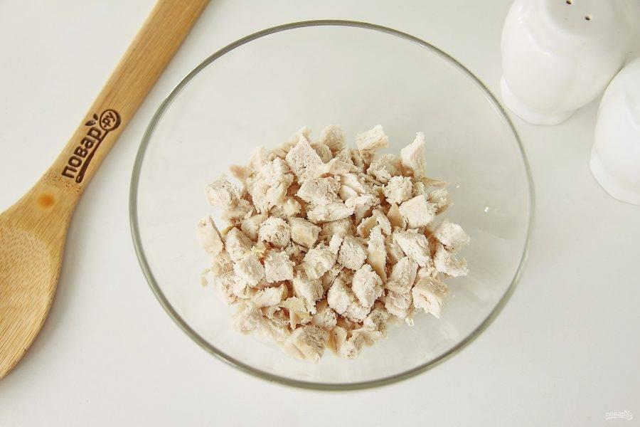 Нарежьте отварное куриное филе небольшими кубиками и сложите в глубокую миску или салатник.