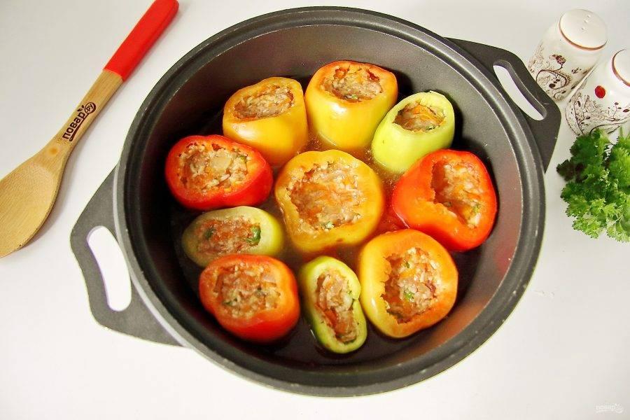 """Нафаршируйте перец подготовленной начинкой и разместите """"стоя"""" в казанке или кастрюльке с толстым дном. Разведите в кипятке томатную пасту, добавьте по вкусу соль и залейте фаршированные перцы так, чтобы вода доходила почти до середины перцев. Накройте емкость крышкой и тушите перцы на небольшом огне 40-50 минут."""