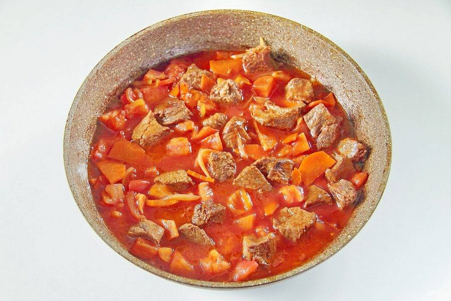 4. Обжаривайте все вместе около пяти минут. Добавьте нарезанный кубиками помидор, предварительно сняв с него шкурку и влейте томатный сок. Накройте сковороду опять крышкой и тушите мясо с овощами на небольшом огне 30 минут.