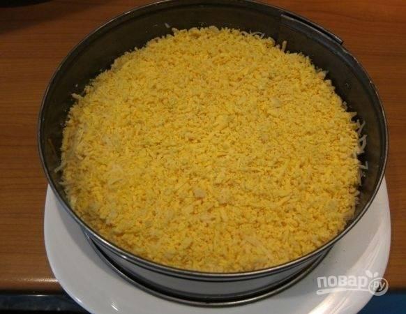 9. Отделите белки и натрите на терке. Выложите ровным слоем, смажьте майонезом. Затем — тертый сыр, снова немного майонеза и желтки. В таком виде отправьте салат в холодильник на 2-3 часа, чтобы он пропитался, а перед подачей аккуратно удалите кольцо.