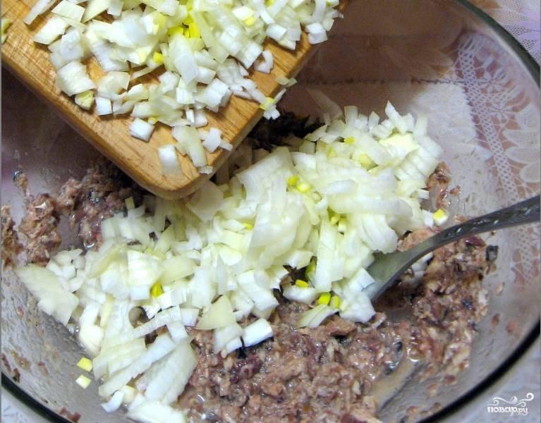 Репчатый лук чистим и нарезаем на мелкие кубики, затем выкладываем его в миску с рыбой и хорошенько перемешиваем.