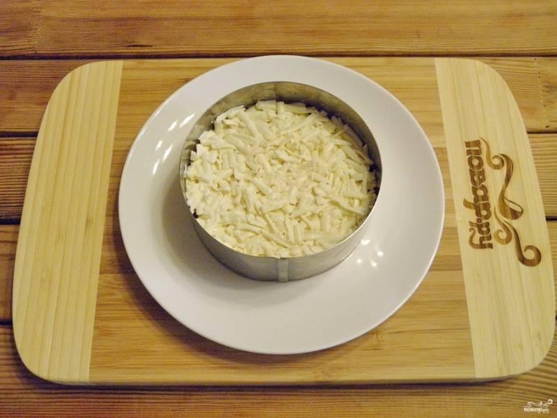 Следующий слой - плавленый сыр. Солить его не нужно, если он соленый. Сделайте только майонезную сеточку.