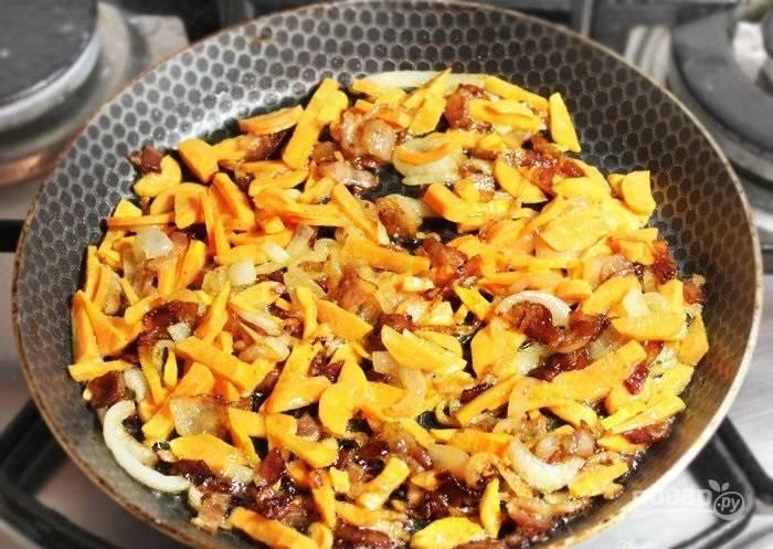 3.Очистите морковь, нарежьте ее тонкими кусочками. Выложите ее в сковороду к луку и бекону.