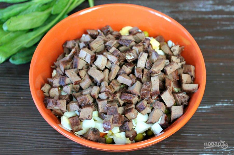 Готовую печень режем кубиками и высыпаем в салат.