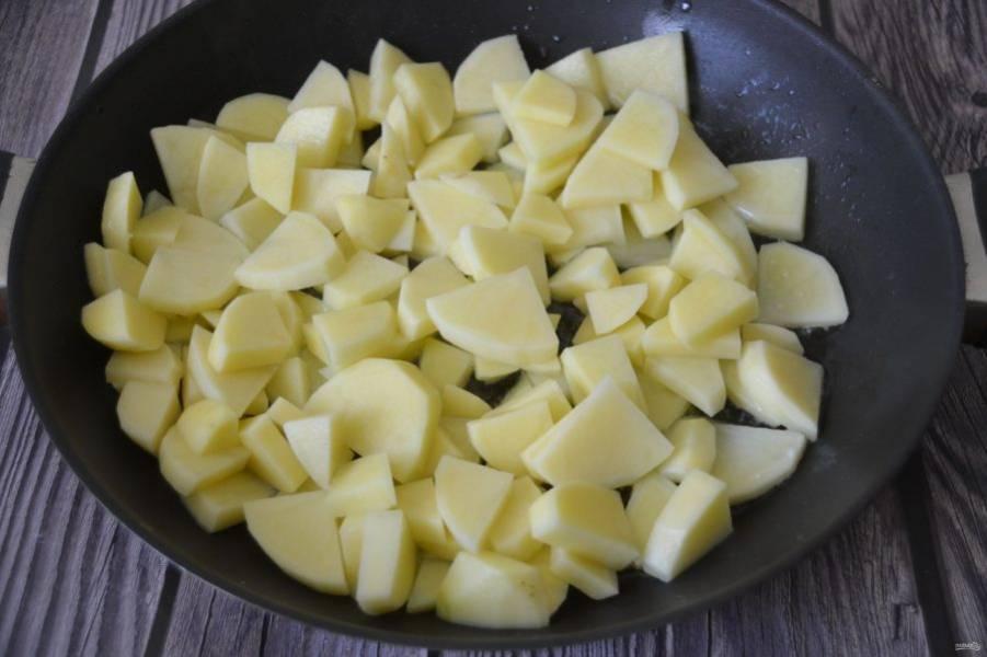 В другой сковороде обжарьте картошку. Для этого хорошо разогрейте сковороду, выложите растительное и сливочное масло и добавьте картофель. Жарьте под крышкой 15 минут.