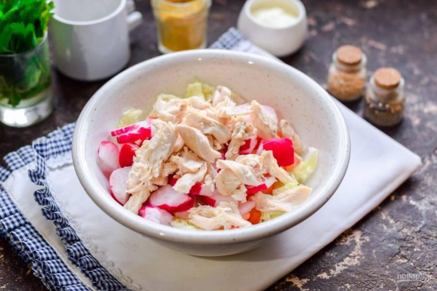 Курицу нарежьте кусочками или порвите на волокна. Переложите курицу в салат.