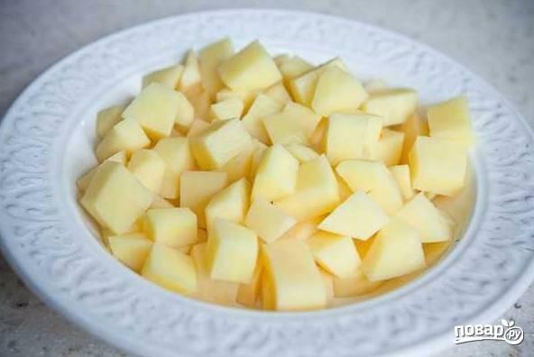 1. Первым делом поставьте на огонь кастрюлю с водой и доведите до кипения. Очистите картофель и нарежьте небольшими кубиками.