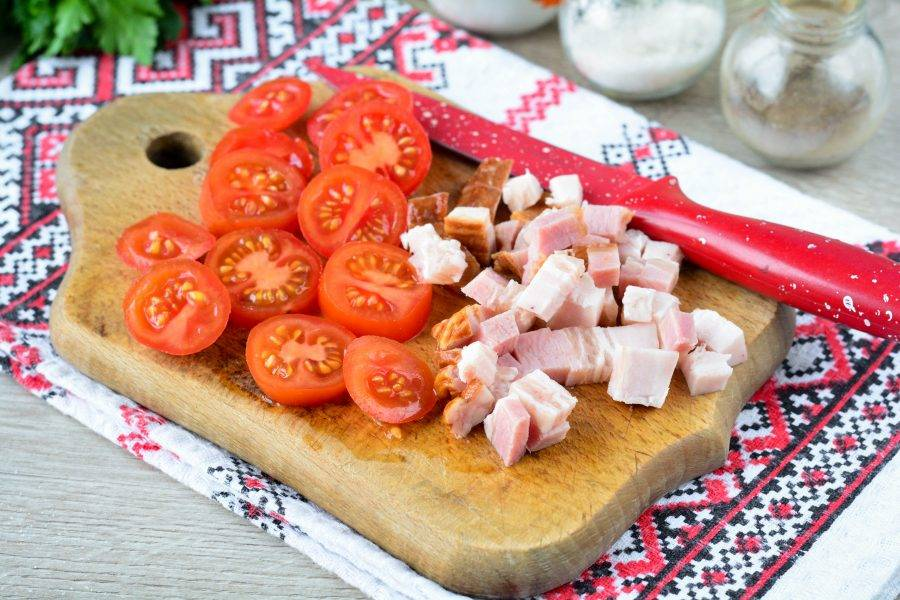 Для начинки нарежьте бекон кубиками, а помидоры дольками.