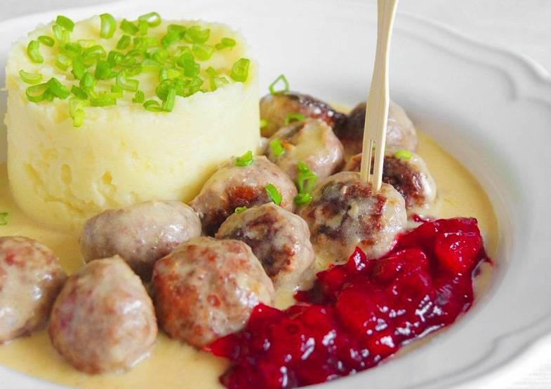 Готовые фрикадельки выложите на тарелку и полейте сливочным соусом. Как правило, фрикадельки подают с картофельным пюре. Ещё одна незаменимая добавка к блюду - брусничное варенье.