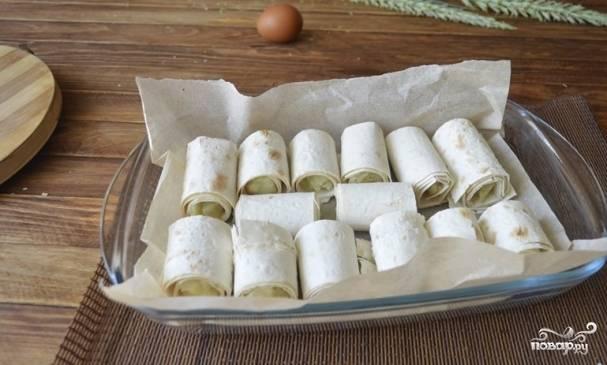 Форму для выпекания застелите пергаментом. Выложите рядами в нее все трубочки.