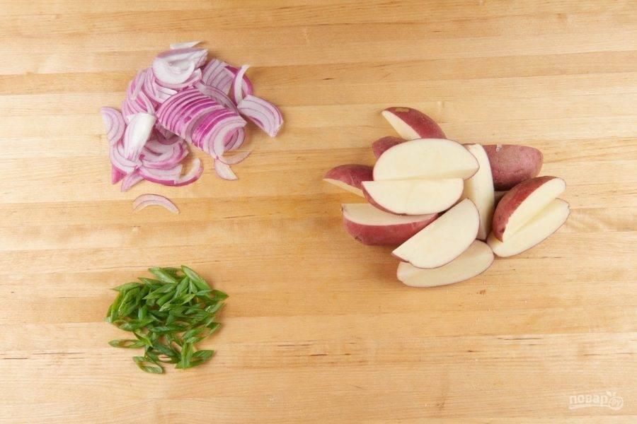1. Подготовьте ингредиенты. Картофель нарежьте дольками. Зелёный лук нашинкуйте под углом, а репчатый — полукольцами. Стейки натрите солью с перцем.