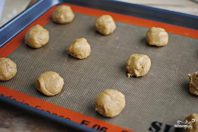 4. Накрыть тесто и поставить в холодильник охлаждаться по крайней мере на 2 часа или на ночь. Разогреть духовку до 175 градусов. Выстелить противень пергаментной бумагой или силиконовым ковриком. Сформировать из теста маленькие шарики размером 2,5 см.