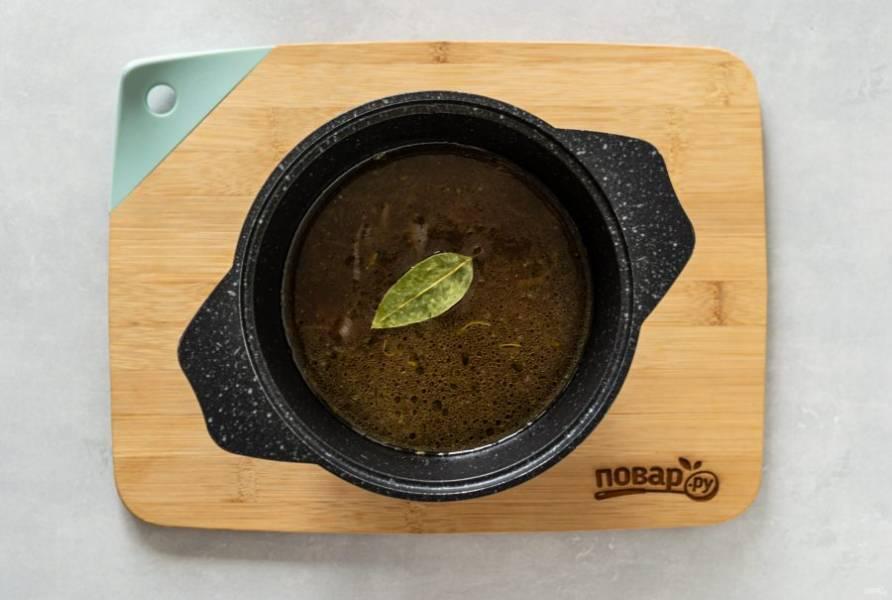 Влейте овощной бульон, добавьте лавровый лист. Доведите до кипения. Накройте кастрюлю крышкой и томите суп на медленном огне еще 20 минут.