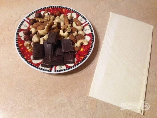 1. Нам понадобится минимум ингредиентов, всего лишь слоеное тесто, немного шоколада и орехи. Тесто предварительно разморозьте, а орехи можно подсушить.