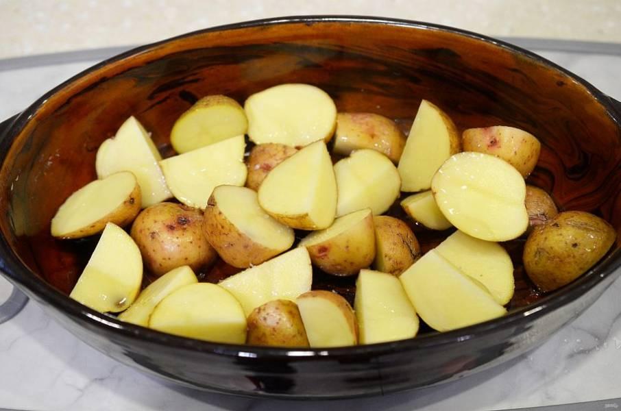 Выложите картофель в жаропрочную форму, полейте растительным маслом.