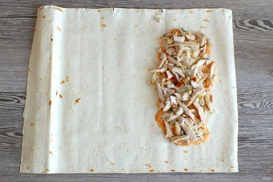 На капусту разложите 1/2 часть курицы.