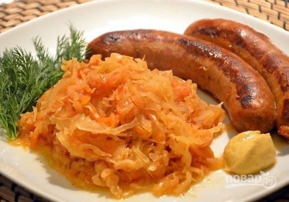 4.После окончания процесса тушения переложите блюдо в тарелку. Подавайте с зеленью, горчицей и колбасками.