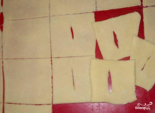 Раскатываем тесто на обсыпанной мукой разделочной доске или прямо на столе. Толщина должна быть минимальная, ведь мы хотим получить тонкий и воздушный хворост. Нарезаем пласт теста на небольшие квадратики, а в середине каждого делаем прорезь.