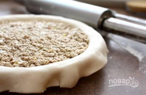 3. Тесто разделите на 2 части и раскатайте. Выложите один пласт в жаропрочную форму, а следом — остывшую немного начинку.
