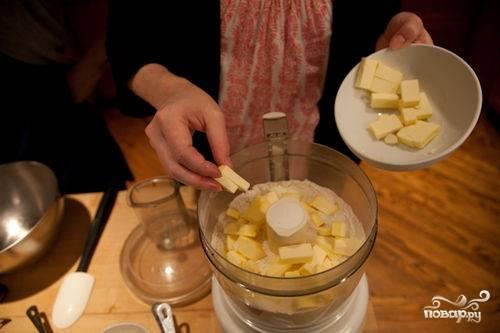 Затем в чашу кухонного комбайна кладем соль сахар и розмарин и измельчаем эти компоненты в течении 30-60 секунд, засыпаем муку, комбайн включаем на секунд 20-30. Затем в чашу добавляем кубиками нарезанное масло. Масло должно быть охлажденным (желательно в морозильнике). Взбиваем все импульсами (по 15 секунд) несколько раз.