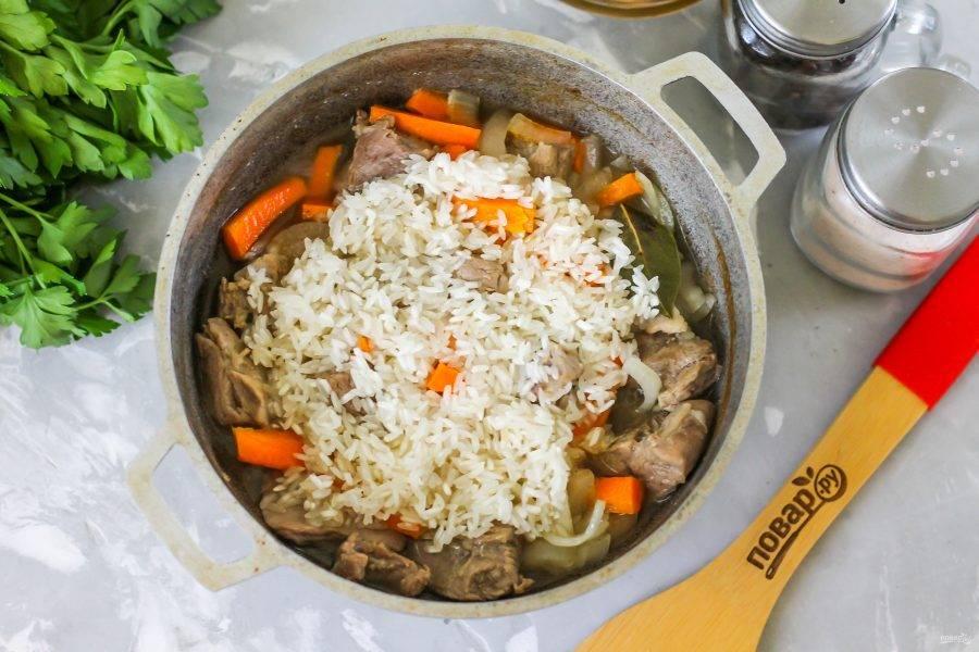 Промойте рис в воде и выложите в казан.