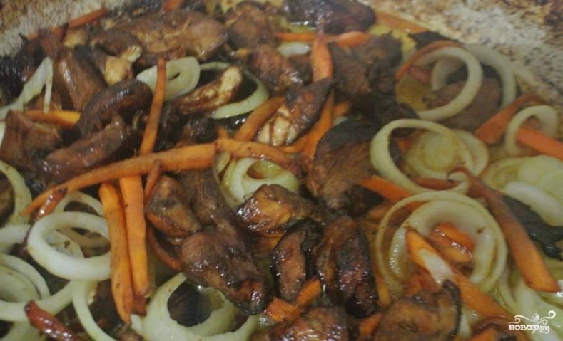 Как только из мяса испарится часть сока, добавляем кольца репчатого лука и тонко нарезанную или тертую морковь. Обжариваем до практически полной готовности овощей.