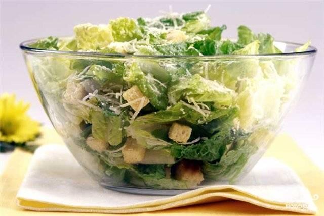 Выложить на салатные листья полоски кальмаров и крутоны, полить оставшимся соусом. посыпать тертым пармезаном и подать на стол!