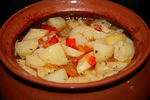 Обжарив еще немного, перекладываем мясо с овощами в горшочек. Добавляем порезанный крупно картофель, соль, перец, тимьян, базилик и душицу. Сверху заливаем водой (примерно на 2/3), кладем пару ложек сметаны. Готовим в духовке 1 час, температура 200 градусов.