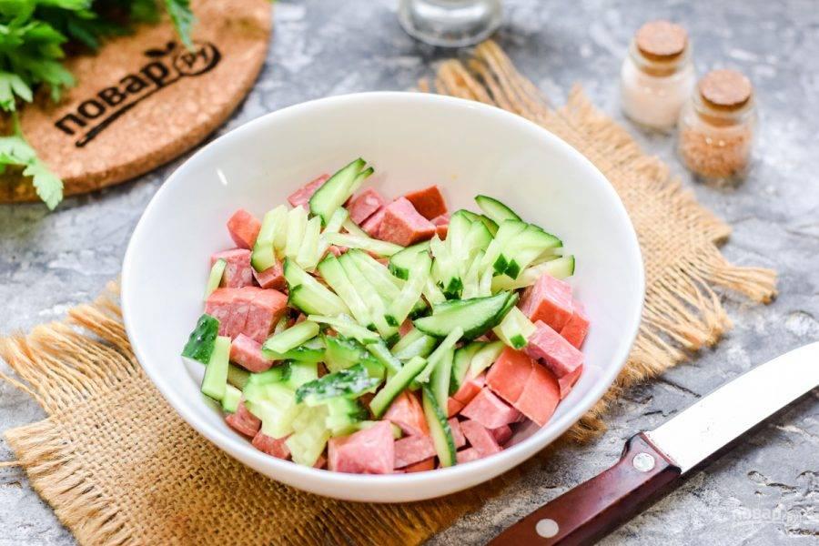 Свежий огурец нарежьте небольшими кусочками и добавьте к колбасе.