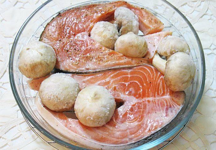 Кладем к рыбе в форму для выпекания вымытые шампиньоны (целиком).