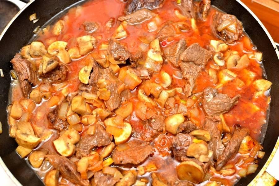 Мелко нарежьте шампиньоны. Выдавите чеснок. Когда лук обжарится до мягкости, выложите всё в сковороду к луку и говядине. Добавьте томатной пасты, муки и говяжьего бульона. Потушите. Посолите и поперчите по вкусу.