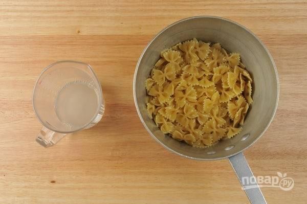 2. Отварите пасту около 11 минут в подсоленной воде. 1/4 воды сохраните. Готовые макароны промойте, затем добавьте ложку масла. Перемешайте.