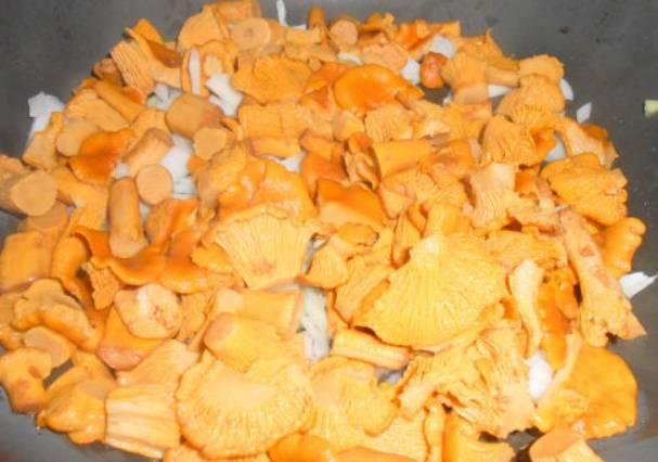 Сваренные грибы откидываем на дуршлаг, чтобы стекла лишняя вода. Затем обжариваем грибы с измельченным луком на растительном масле. Жарим 5-7 минут.