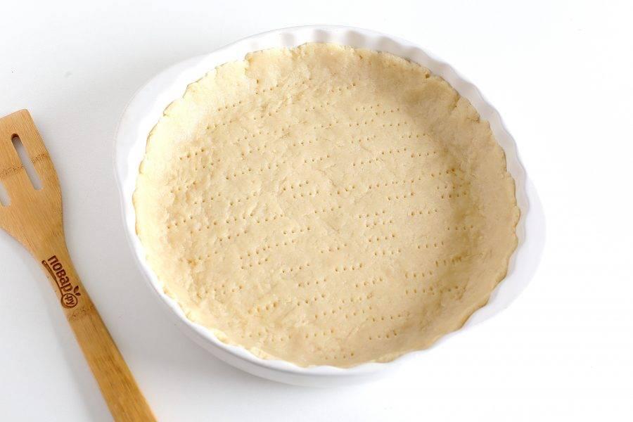 Разделите тесто на две неравные части. Ту часть, что поменьше, заверните и уберите пока в холодильник. Вторую часть раскатайте и переложите аккуратно в смазанную маслом форму. Руками придайте ему нужный размер и сформируйте бортики. Дно наколите вилкой.