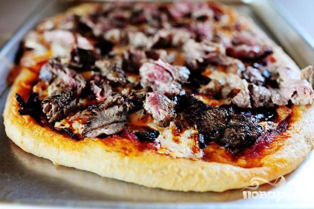 6. Пока пицца готовится, нарезать стейк на очень тонкие ломтики. Убрать пиццу из духовки и выложить ломтики стейка по всей поверхности. Полить сверху соусом для стейка и посыпать тертым Пармезаном. Нарезать на квадраты и сразу же подавать.