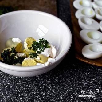 3.  Смешать желтки с майонезом, горчицей, Вустерширским соусом (если используется), лимонным соком и 1 столовой ложкой измельченной петрушки. Обильно приправить солью и молотым черным перцем. Отложить в сторону.