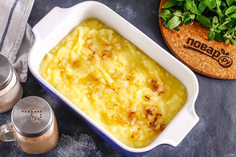 Выложите в форму половину картофельного пюре, а на него — обжаренный лук.